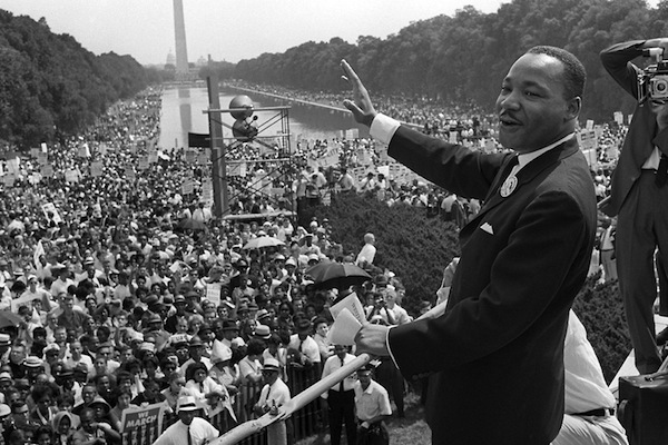 "WASHINGTON, UNITED STATES: US civil rights leader Martin Luther King,Jr. (C) waves to supporters from the steps of the Lincoln Memorial 28 August 1963 on the Mall in Washington DC (Washington Monument in background) during the ""March on Washington."" (Photo credit should read AFP/AFP/Getty Images)"