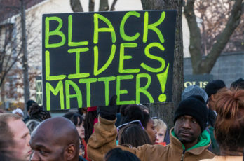 "An activist holds a ""Black Lives Matter"" signs outside the Minneapolis Police Fourth Precinct building following the officer-involved shooting of Jamar Clark on November 15, 2015. Photo: Tony Webster tony@tonywebster.com"