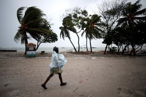 A woman protects herself from rain as Hurricane Matthew approaches in Les Cayes, Haiti, October 3, 2016. REUTERS/Andres Martinez Casares