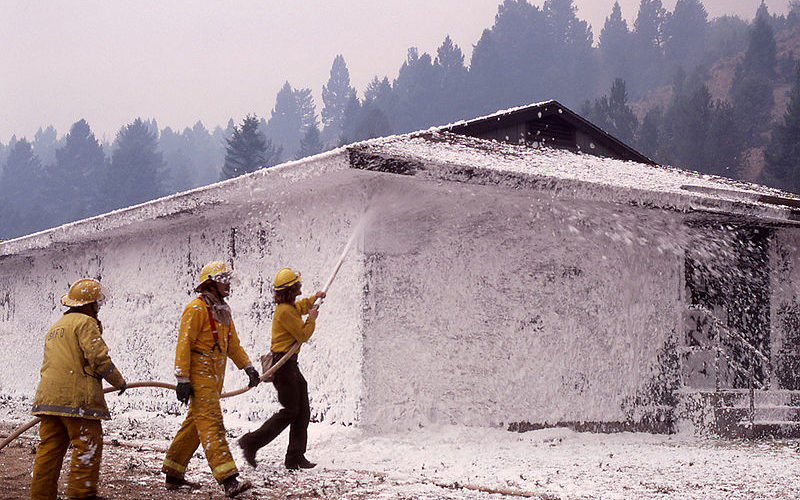 Firefighter using foam to put out a fire