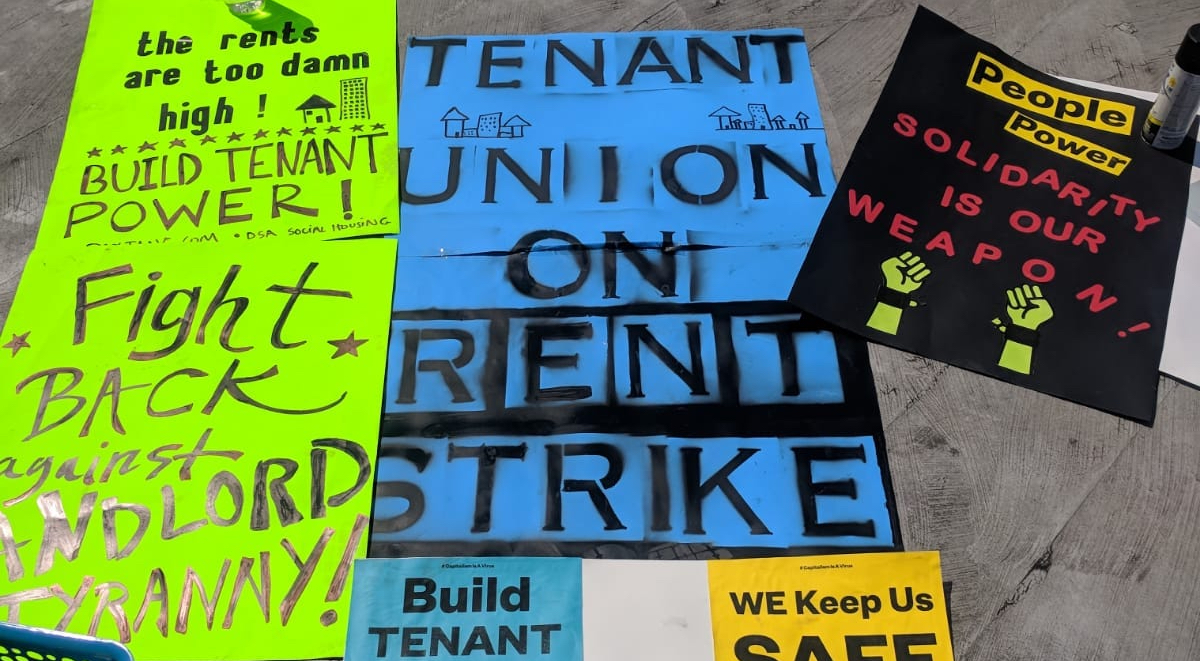 """Protest signs reading """"the rents are too damn high,"""" """"tenant union on rent strike,"""" and """"people power - solidarity is our weapon"""""""
