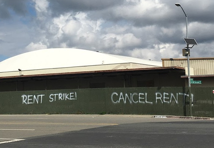 Spray paint on a fence in Oakland reads, rent strike, cancel rent