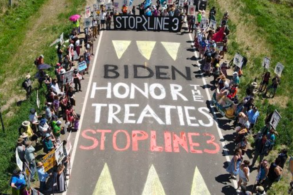 """At the Treaty People Gathering, hundreds gather around road art that says """"Biden - Honor The Treaties, Stop Line 3"""""""