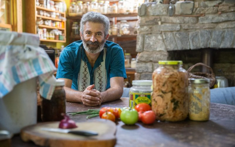Sandor Katz surrounded by jars of fermented foods, vegetables in a kitchen