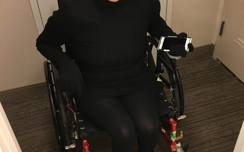Sydney Pickern> A woman using a wheelchair crosses a threshold with her phone in one gloved hand. She wears black from boots to high necked top. Her hair is short on one side and crosses her forehead on the other. Head tilted to one side, she smiles engagingly.