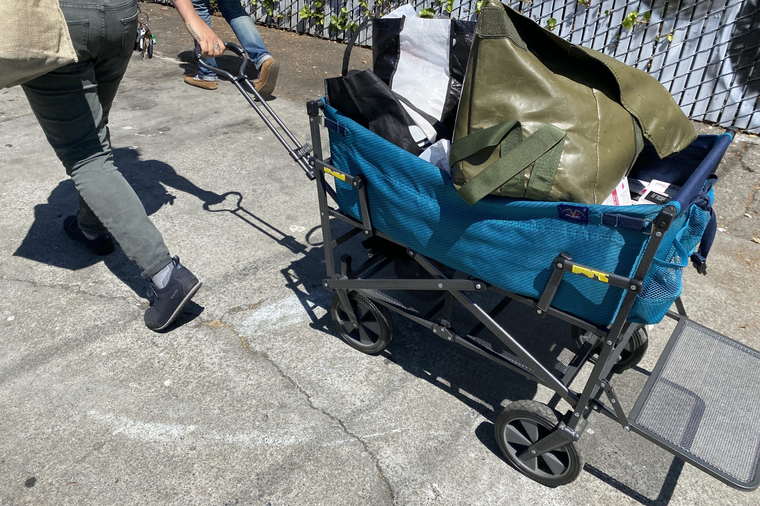 An outreach worker with West Oakland Punks With Lunch pulls a handcart with sterile supplies in West Oakland.