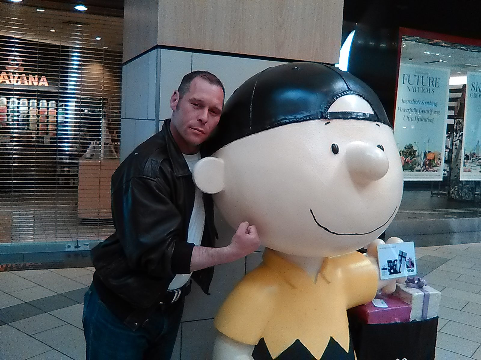 Photo of man smiling and holding his fist to a charlie brown statue in Santa Rosa