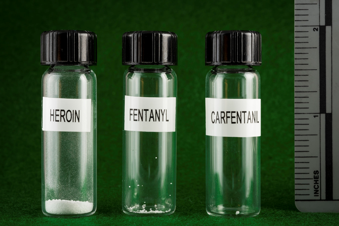Three vials, labeled fentanyl, heroin and carfentanil, comparing equivalent potent doses of each.