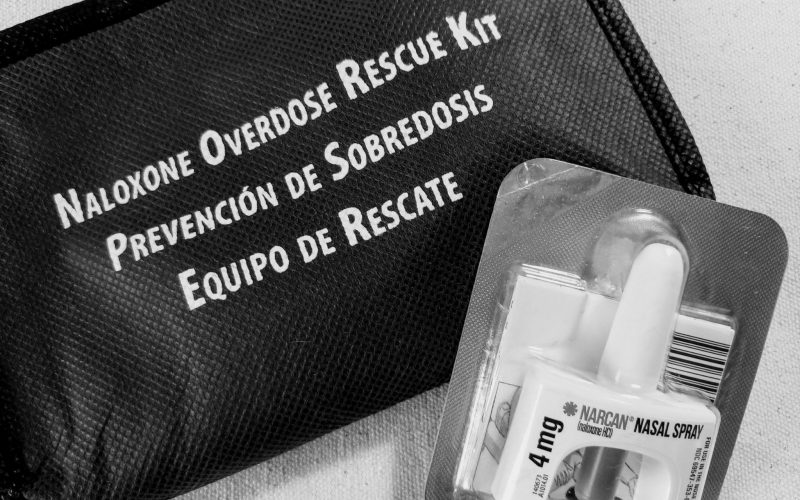 """A black and white photo of a zipper bag that says """"Naloxone overdose rescue kit"""" with a single dose of nasal spray Narcan"""